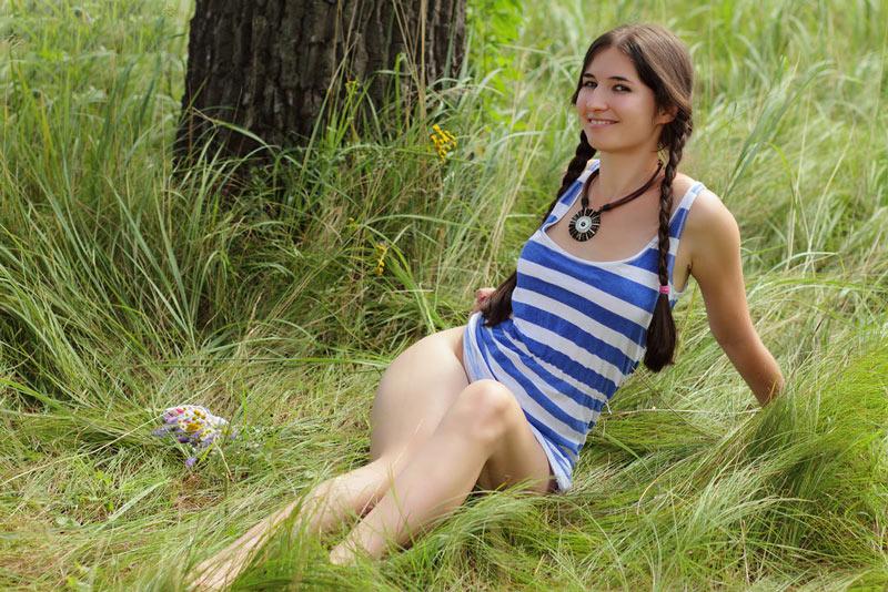 Красивая девушка показала киску на покрывале в лесу